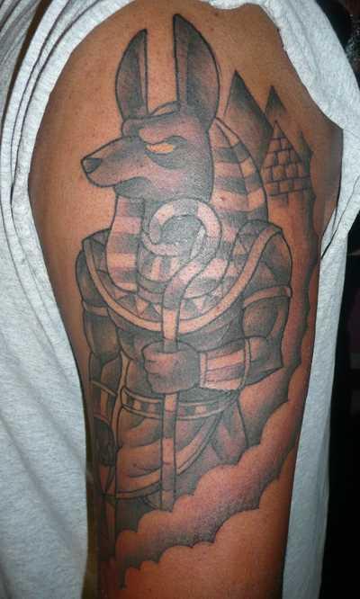 Tatuagem no ombro de um cara - anubis e pirâmide