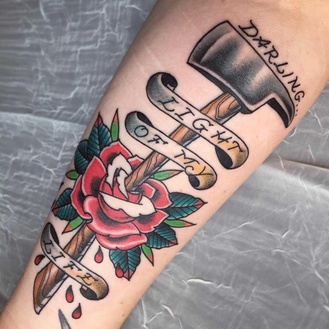 A figura de um machado com uma rosa no antebraço cara