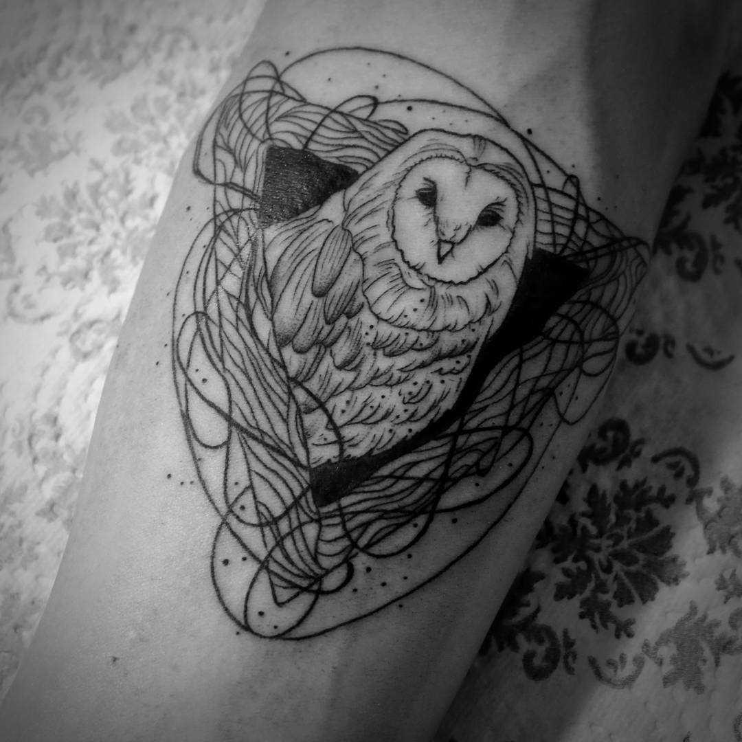 A foto da tatuagem de coruja em um estilo de gráfico no antebraço cara