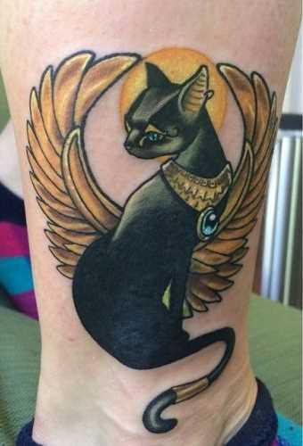 A foto da tatuagem de gato em estilo egípcio sobre a perna da menina