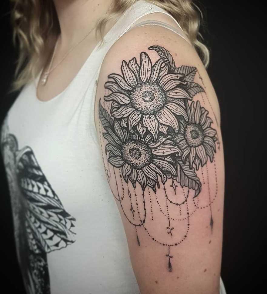 A foto da tatuagem de girassóis, com um padrão no ombro da menina
