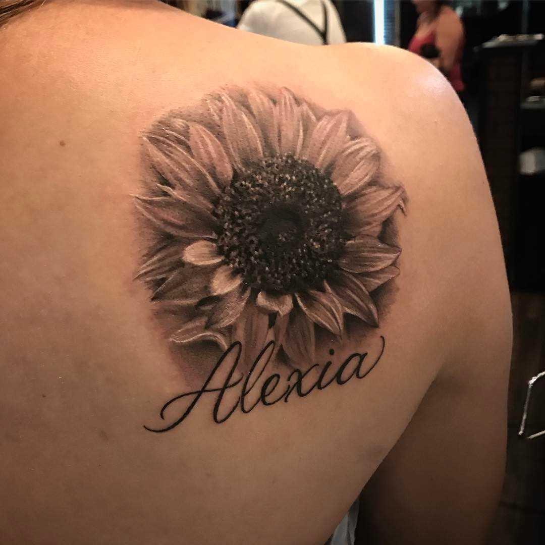 A foto da tatuagem de girassol, com a inscrição na lâmina de uma menina