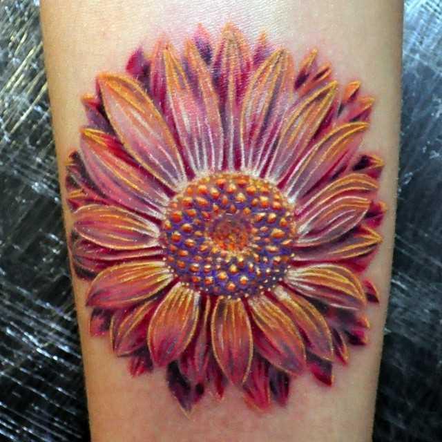 A foto da tatuagem de girassol no antebraço da menina