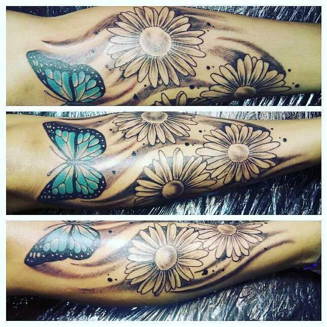 A foto da tatuagem de margaridas com uma borboleta na perna da menina