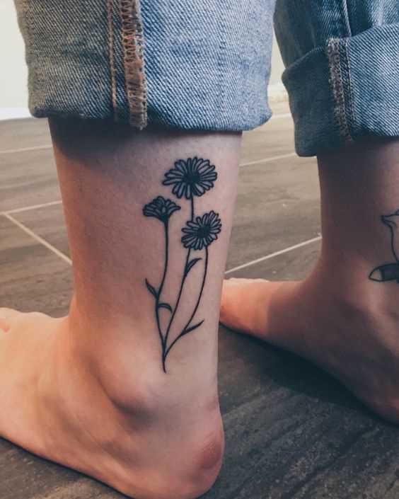 A foto da tatuagem de margaridas sobre a perna da menina