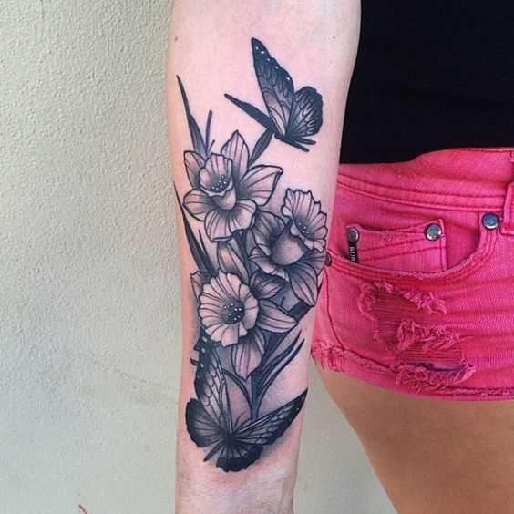 A foto da tatuagem de narciso com borboletas no antebraço da menina