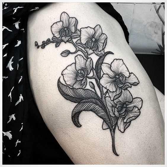 A foto da tatuagem de orquídeas na coxa da menina