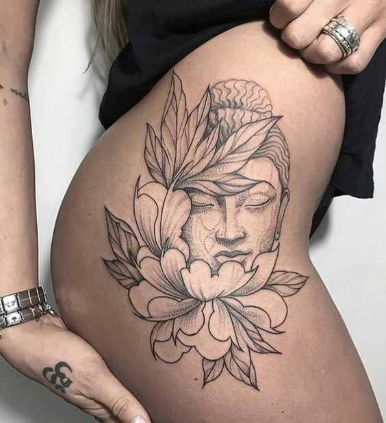 A foto da tatuagem de um buda em estilo indiano, sobre o quadril da menina