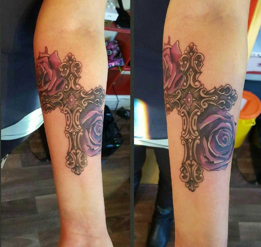 A foto da tatuagem de uma cruz com as rosas em estilo gótico no antebraço da menina