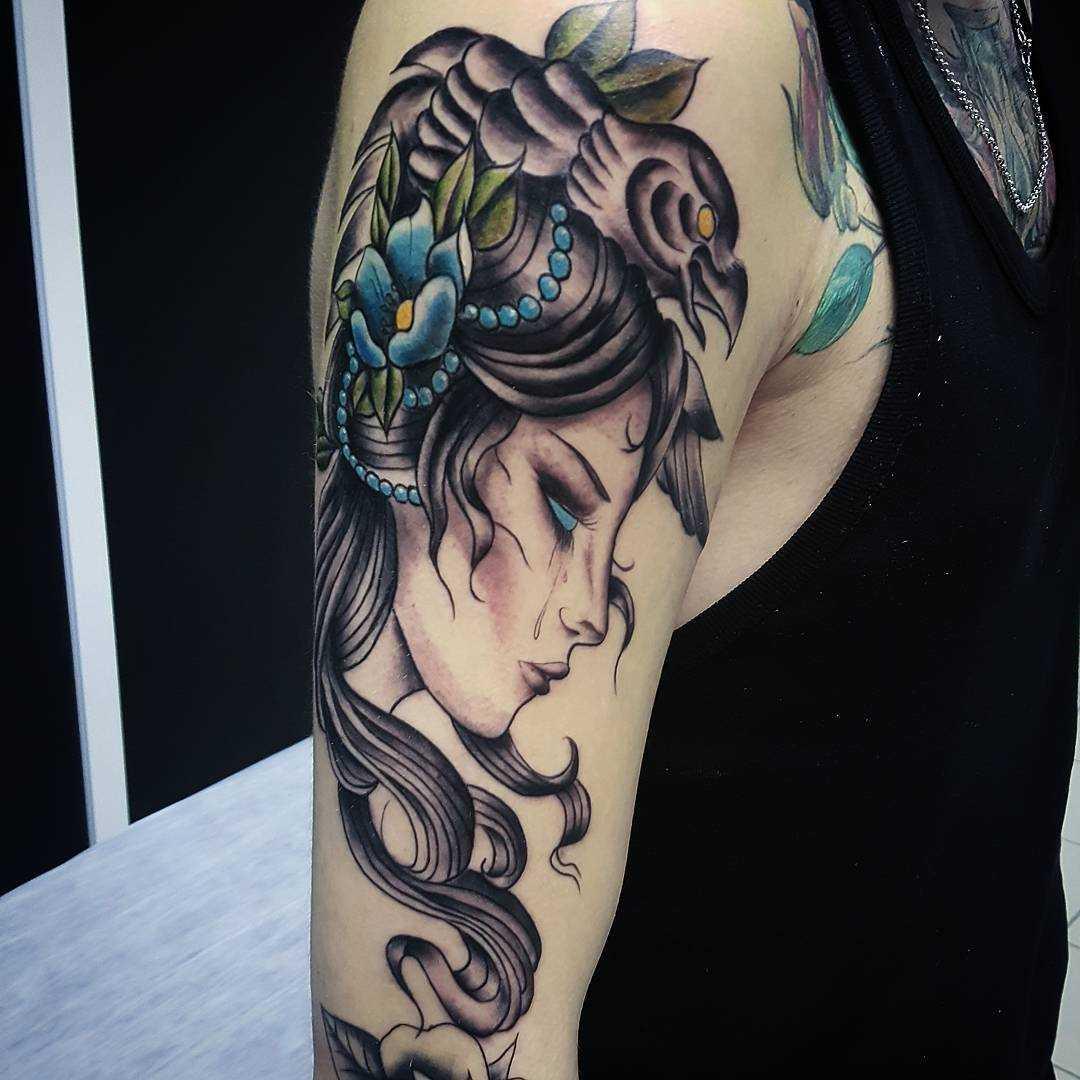 A foto da tatuagem de uma menina no estilo newschool no ombro da menina