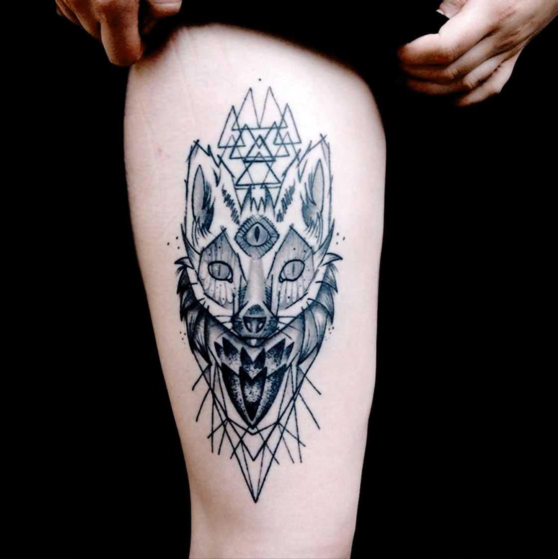 A foto da tatuagem de uma raposa no estilo de gráfico no quadril da menina