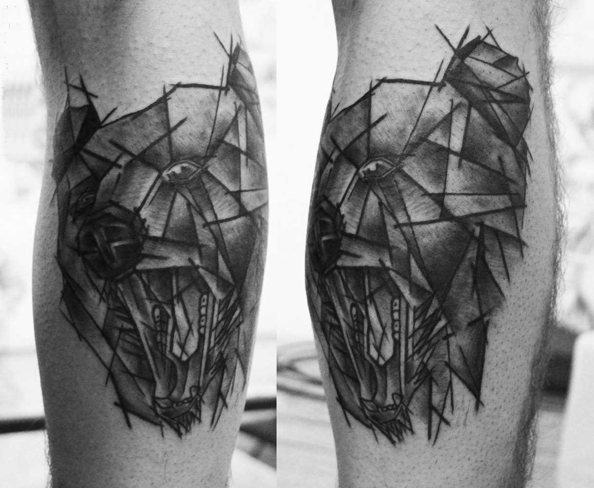 A foto da tatuagem de urso no estilo de um gráfico sobre a perna de um cara