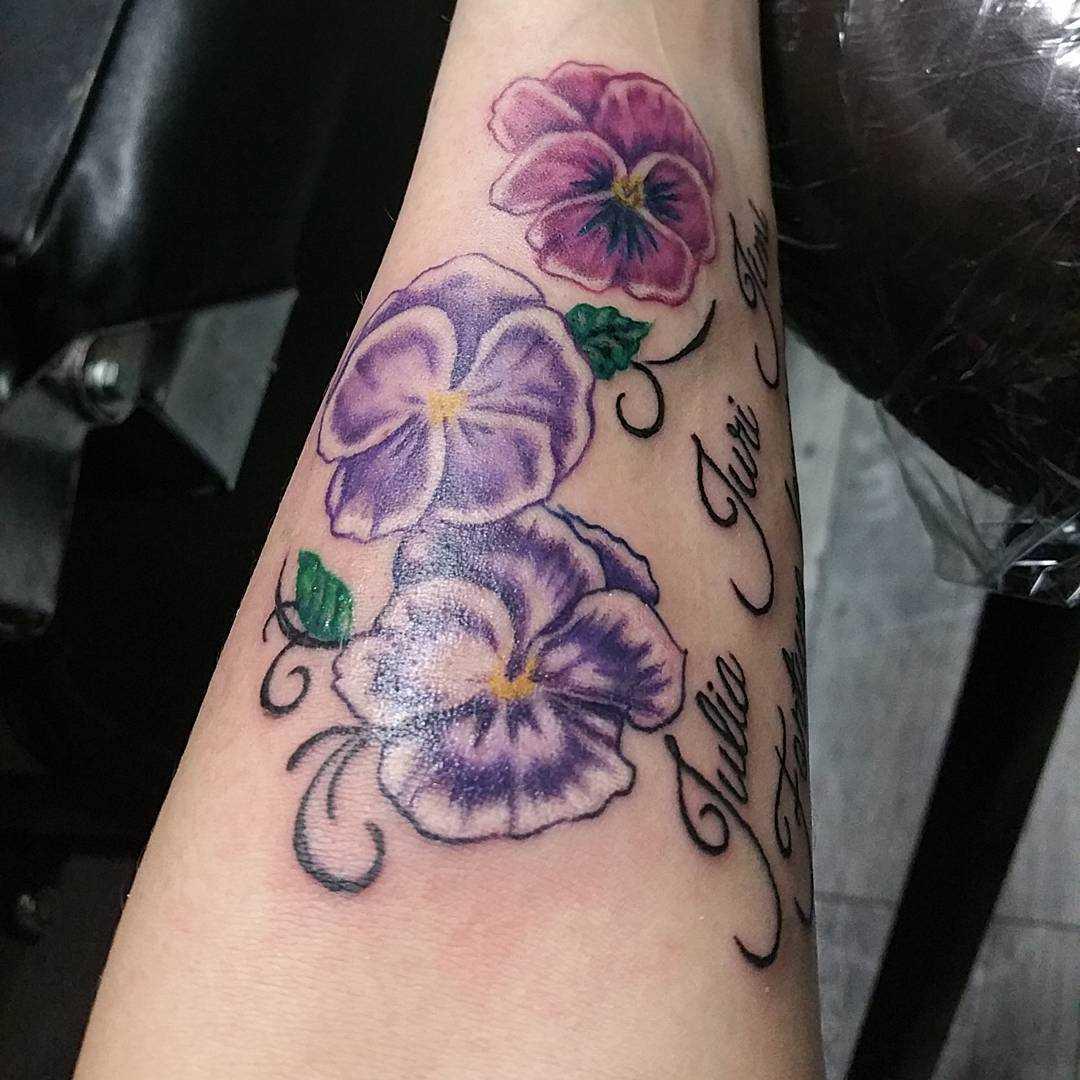 A foto da tatuagem de violetas, com a inscrição no antebraço da menina