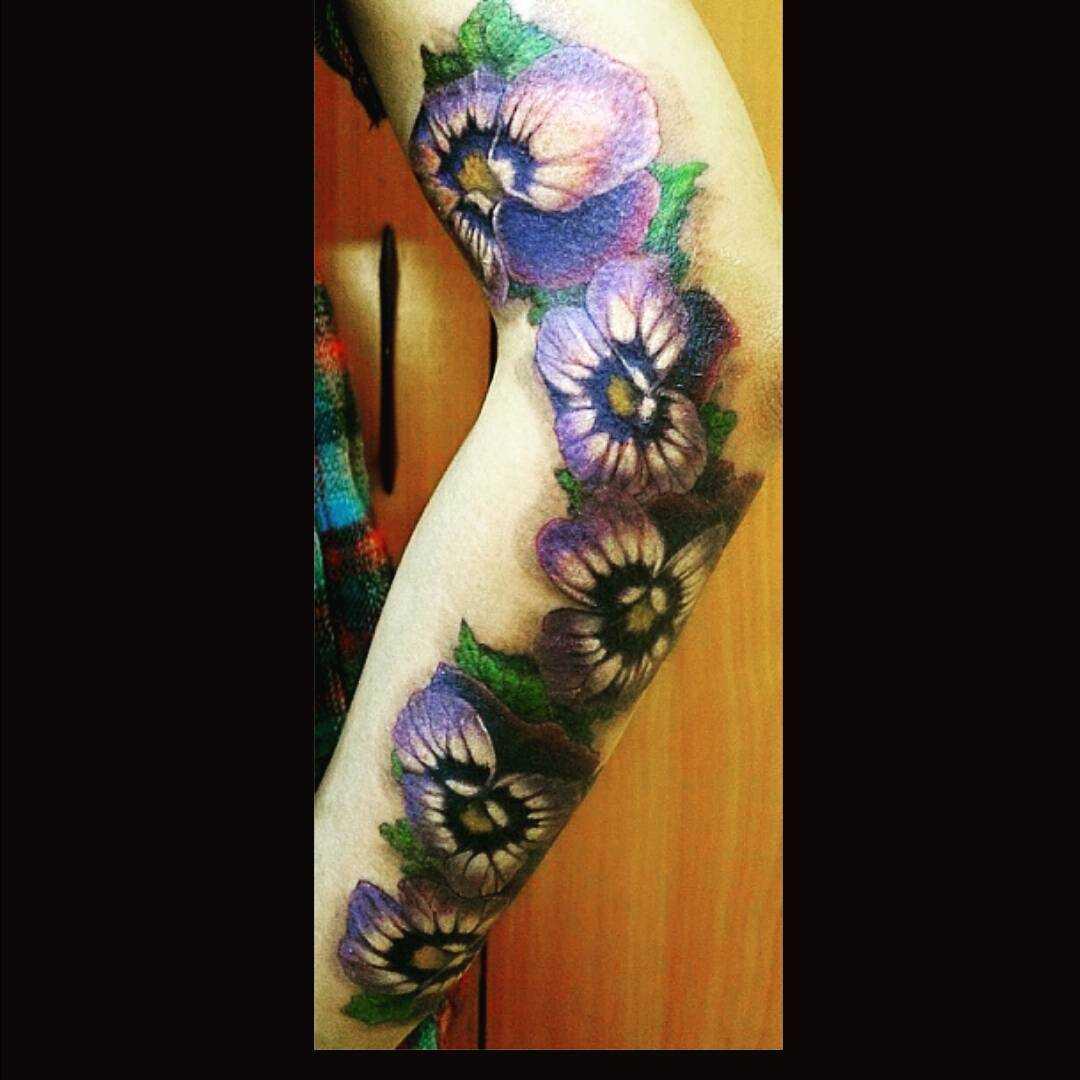 A foto da tatuagem de violetas na mão da menina