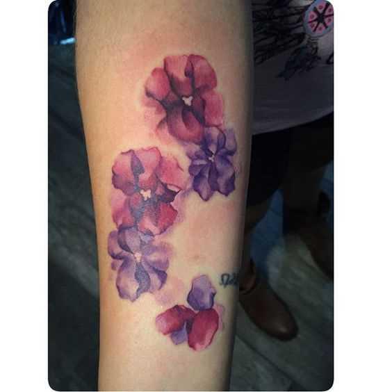 A foto da tatuagem de violetas no estilo aquarela no antebraço da menina