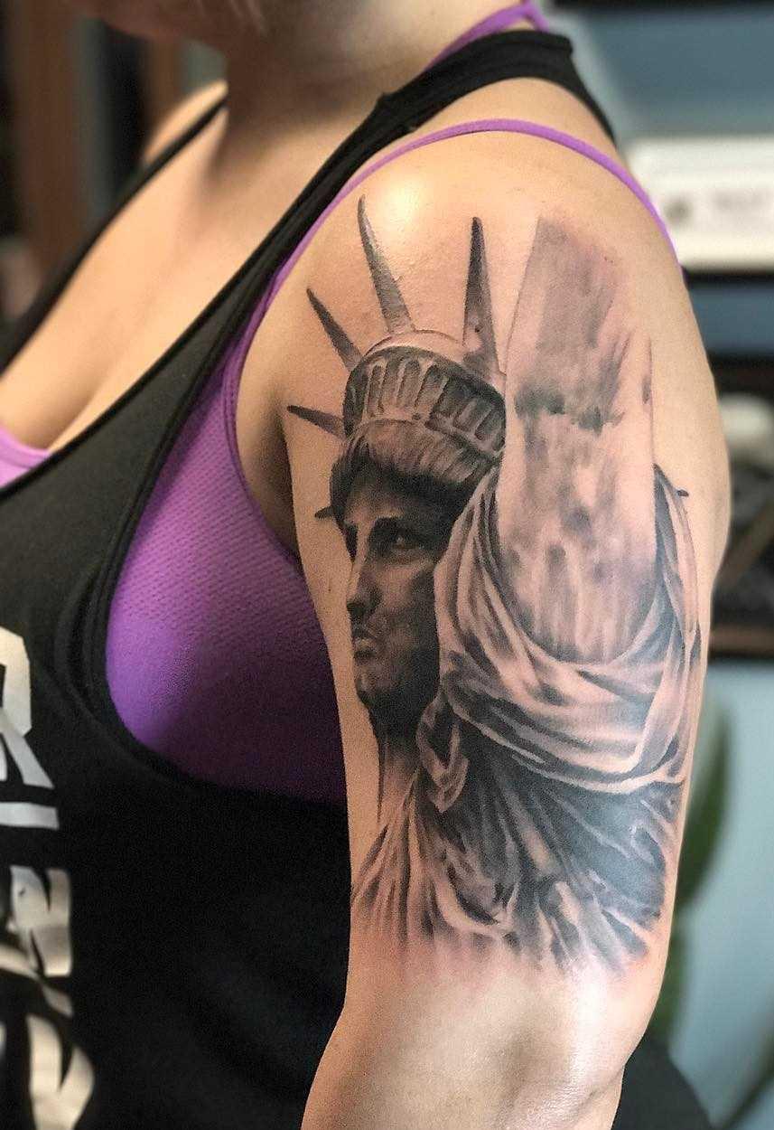 A imagem da estátua da liberdade no ombro de uma mulher