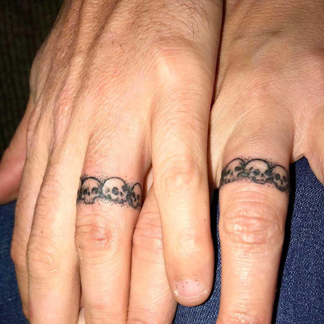A imagem de alianças de casamento em que os dedos de um cara e uma menina