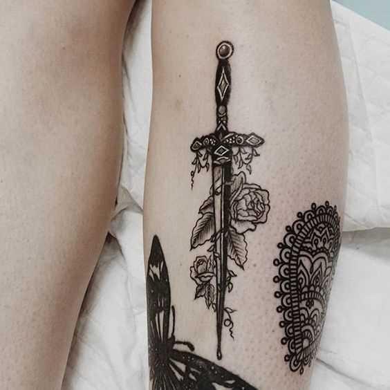 A imagem de uma espada com flores sobre a perna da menina