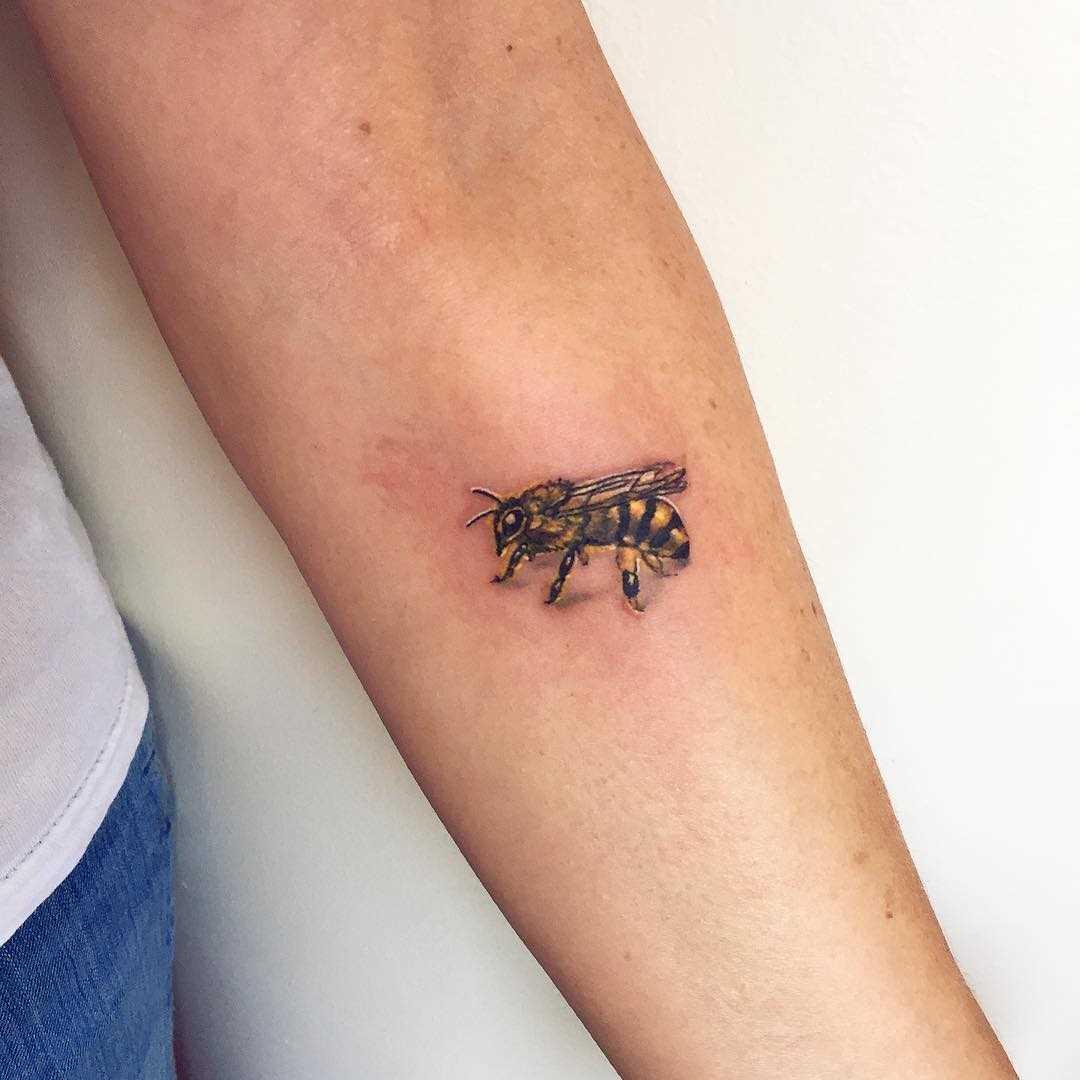 A pequena figura da abelha no antebraço da mulher