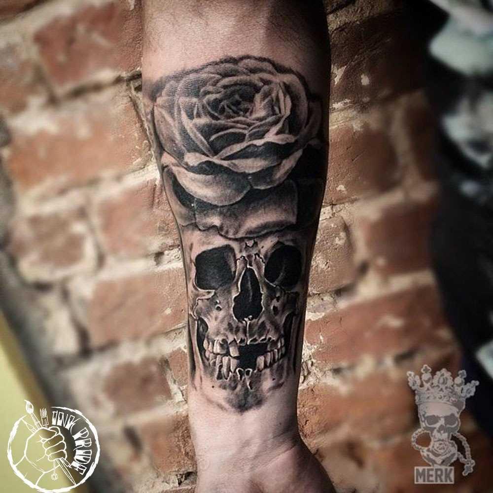 A rosa e o crânio de uma tatuagem no antebraço cara