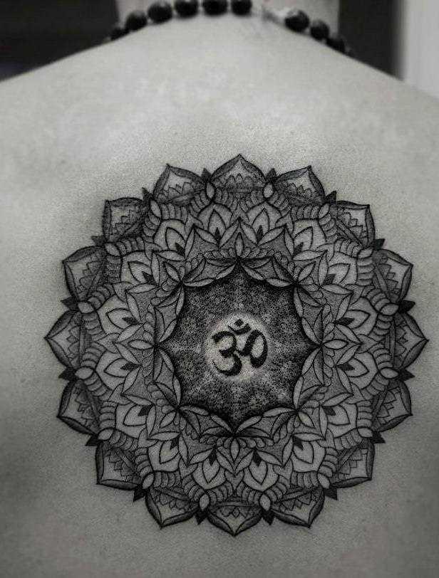A tatuagem da coluna vertebral, a menina - mandala e o símbolo Ohm