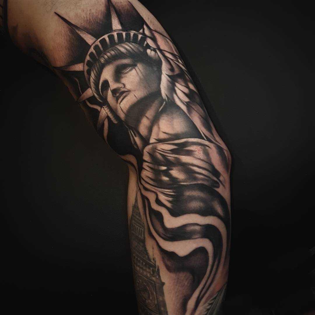 A tatuagem da estátua da liberdade na mão de homens