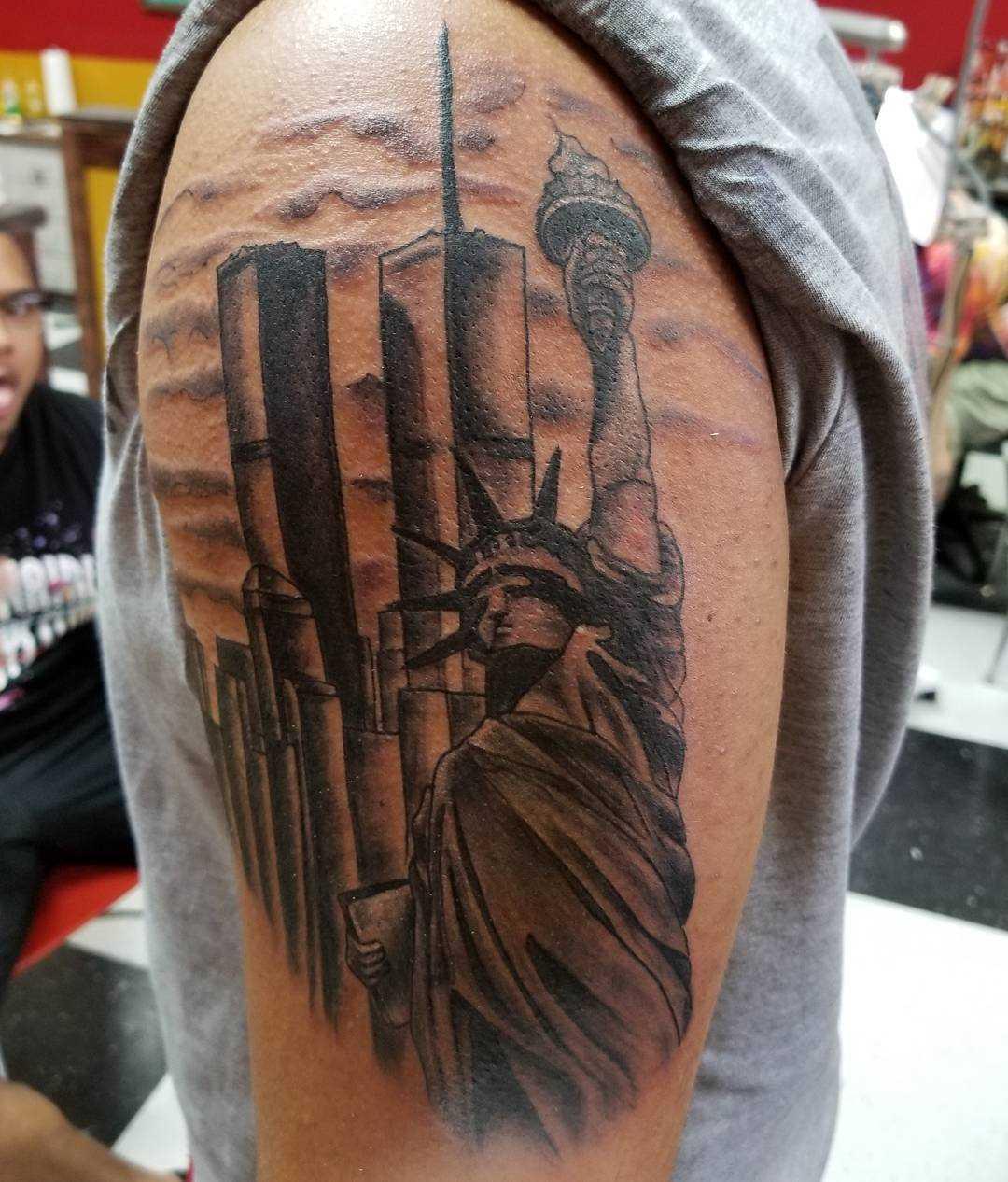 A tatuagem da estátua da liberdade no ombro de homens