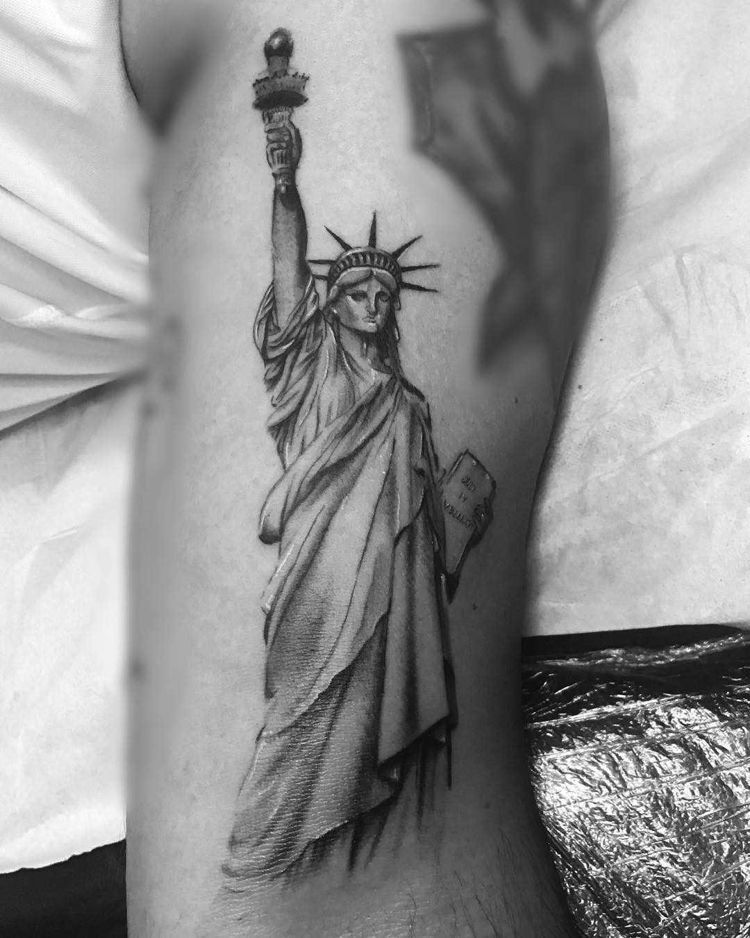 A tatuagem da estátua da liberdade no ombro de um cara