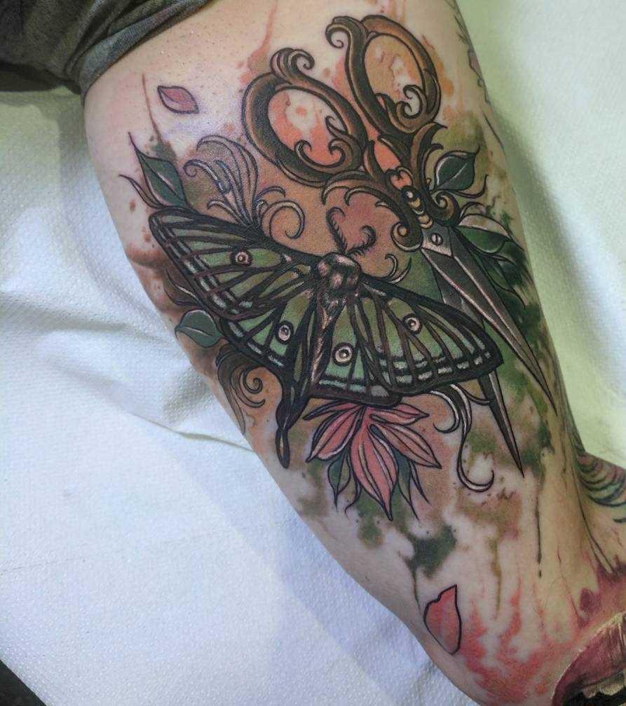 A tatuagem da tesoura com uma borboleta na mão de um cara
