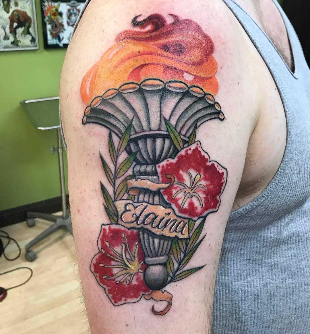 A tatuagem da tocha com flores no ombro de homens