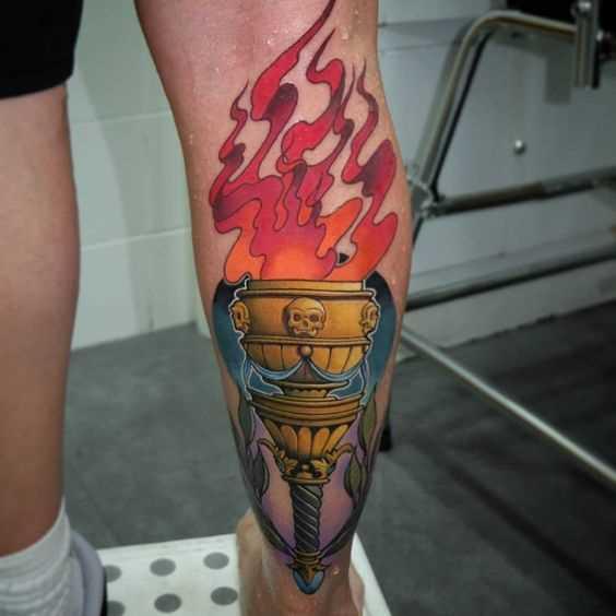 A tatuagem da tocha sobre a perna de um cara