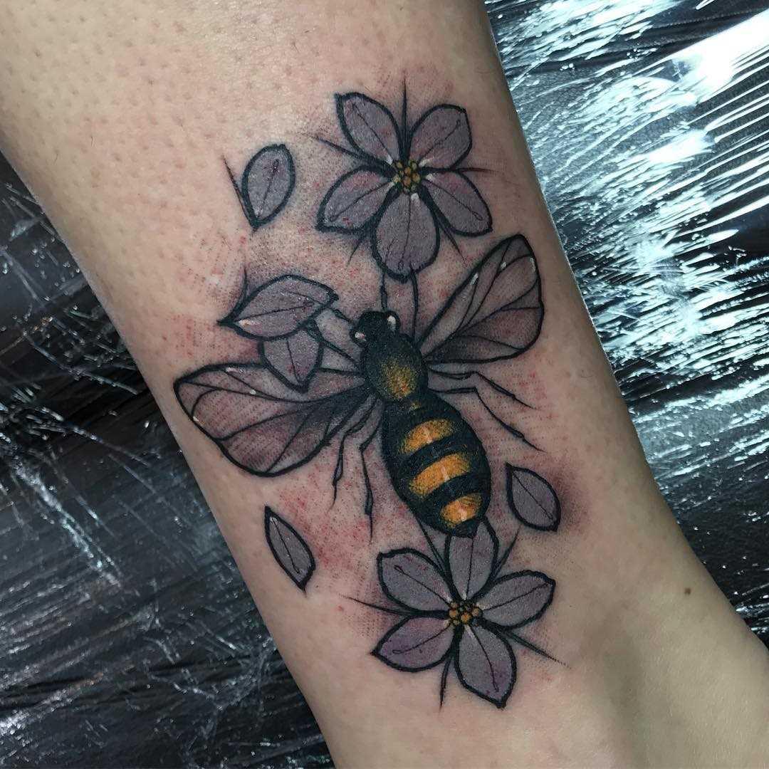 A tatuagem de abelhas com flores sobre a perna da mulher