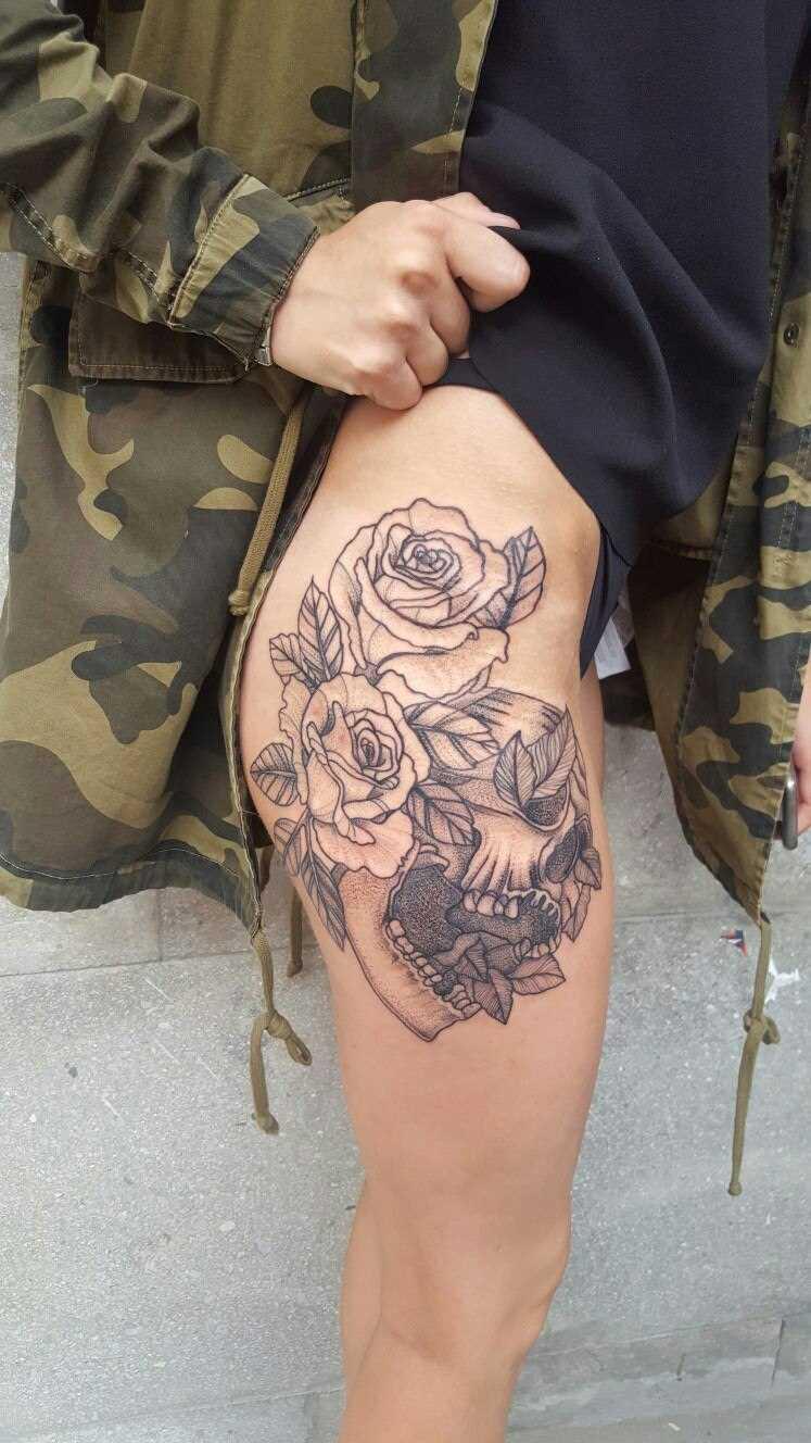 A tatuagem de caveira e rosas em seu quadril da menina
