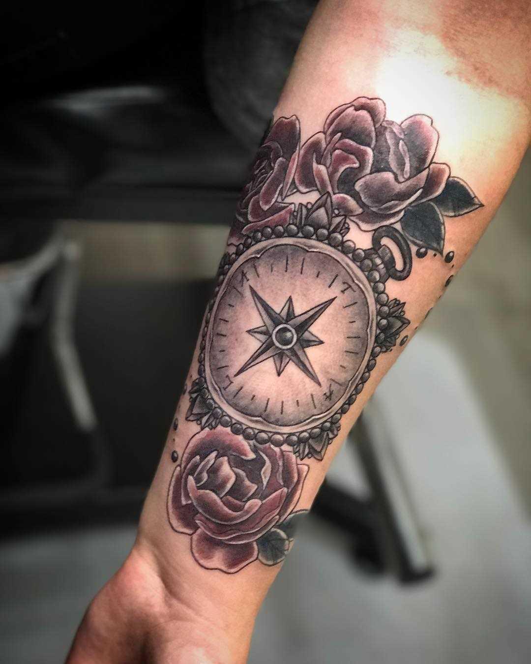 A tatuagem de compasso com as rosas no antebraço da mulher