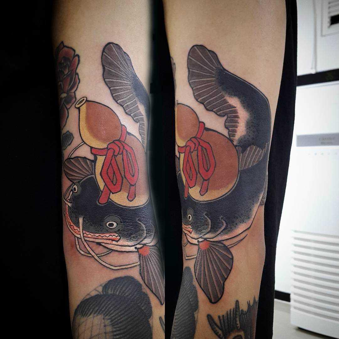 A tatuagem de peixe-gato na mão do cara