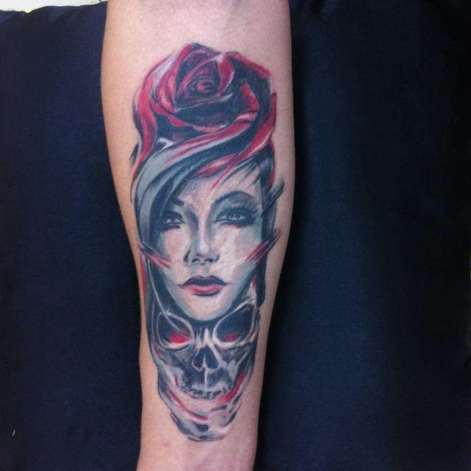 A tatuagem de rosa, a menina e o crânio no antebraço, as meninas