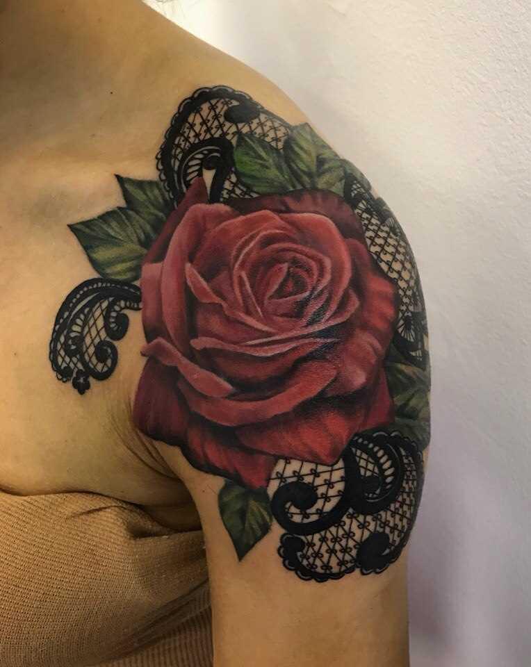 A tatuagem de rosa com rendas padrão no ombro da menina