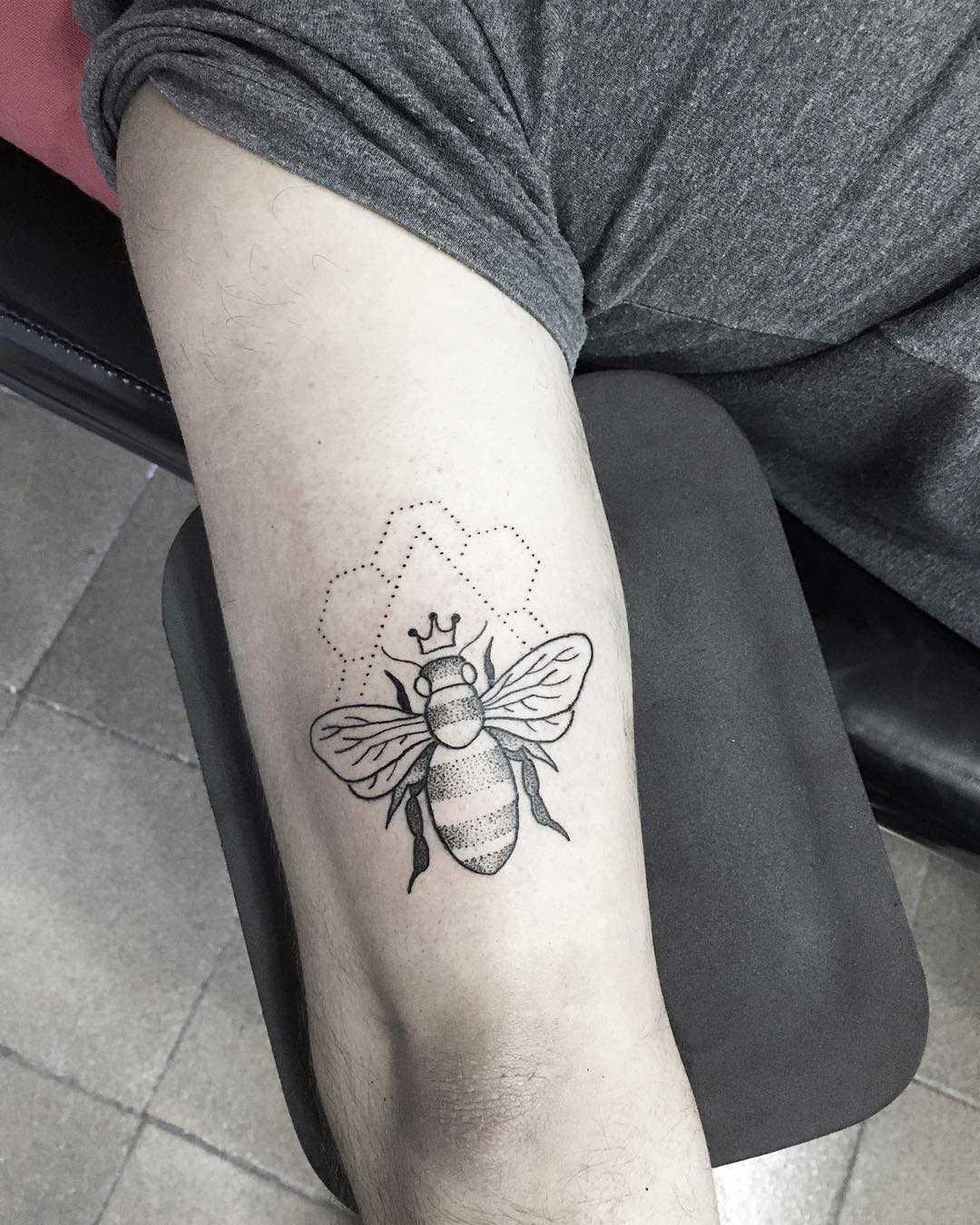 A tatuagem de uma abelha na mão de homens