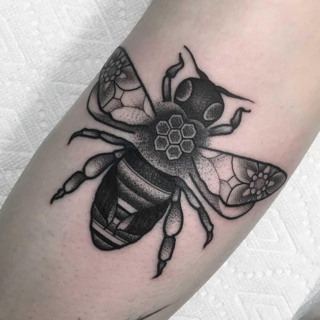 A tatuagem de uma abelha sobre a perna da menina