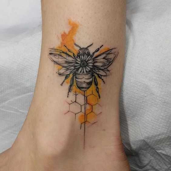 A tatuagem de uma abelha sobre a perna da mulher