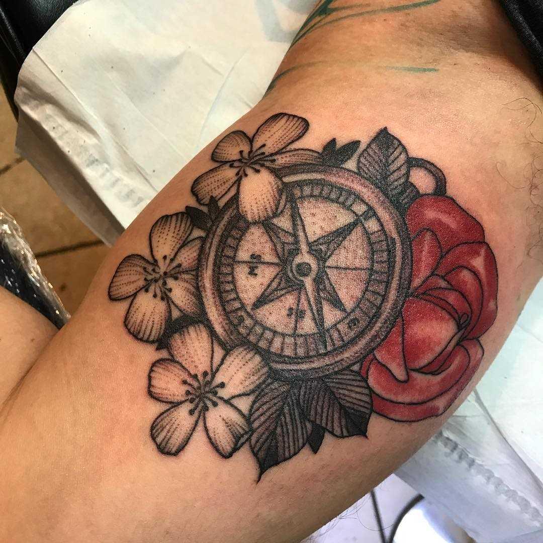 A tatuagem de uma bússola, com flores na mão de homens