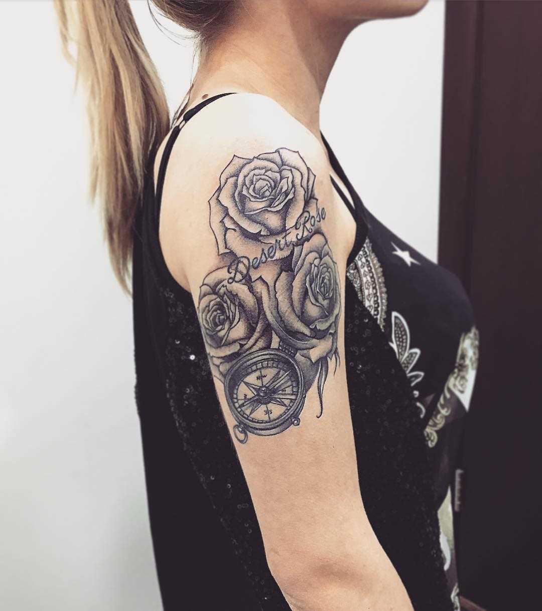 A tatuagem de uma bússola, com rosas no ombro da mulher