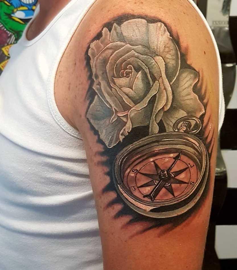 A tatuagem de uma bússola, com uma rosa no ombro do cara