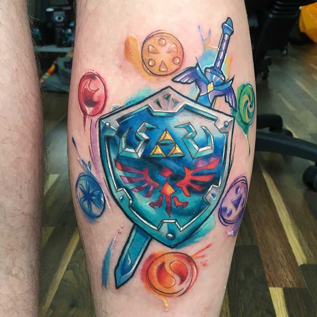 A tatuagem de uma espada com escudo sobre a perna de um cara