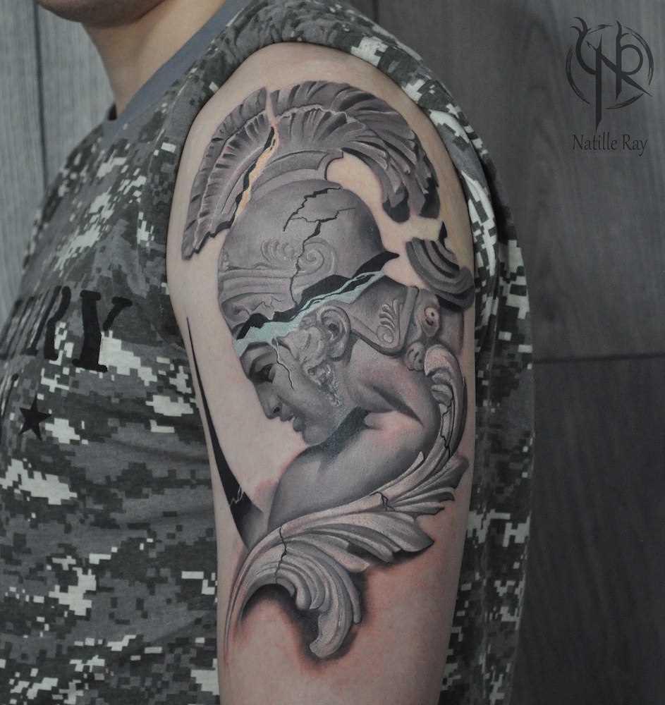 A tatuagem de uma estátua no ombro do cara