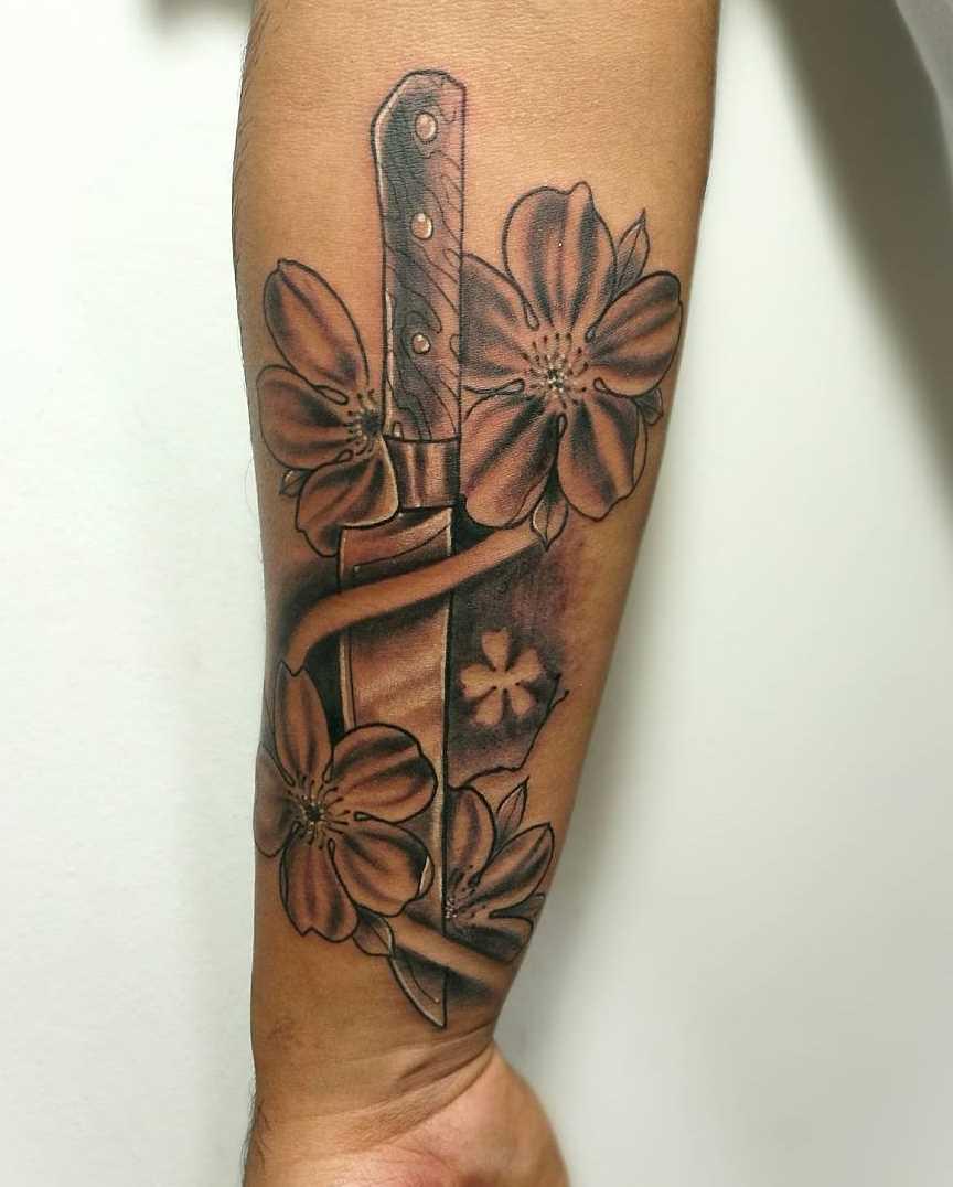 A tatuagem de uma faca com flores no antebraço cara