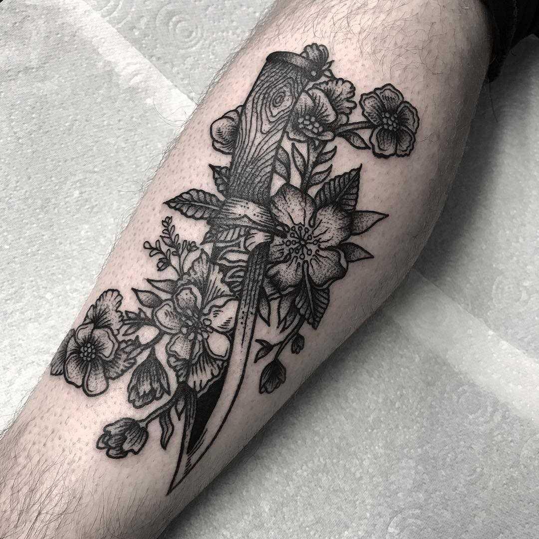 A tatuagem de uma faca com flores sobre a perna de homens