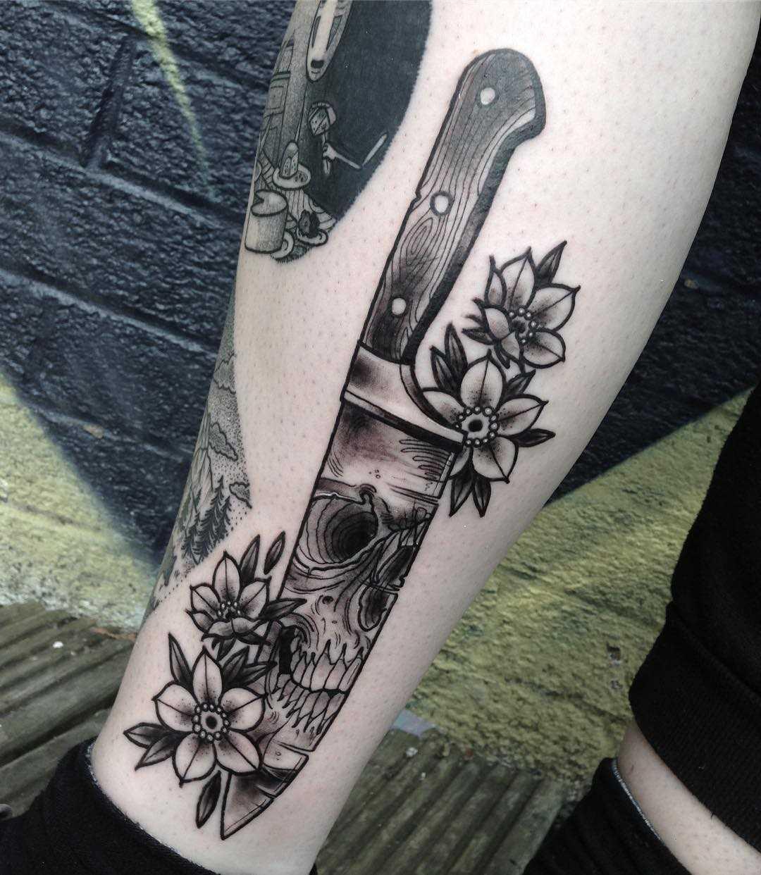 A tatuagem de uma faca com uma caveira e flores sobre a perna da mulher