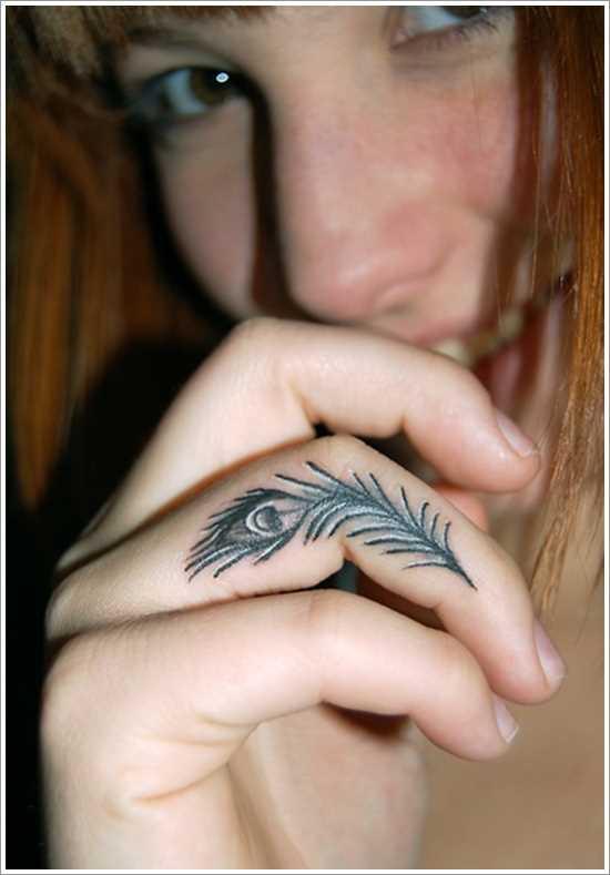 A tatuagem de uma menina em seu dedo em forma de caneta pavão