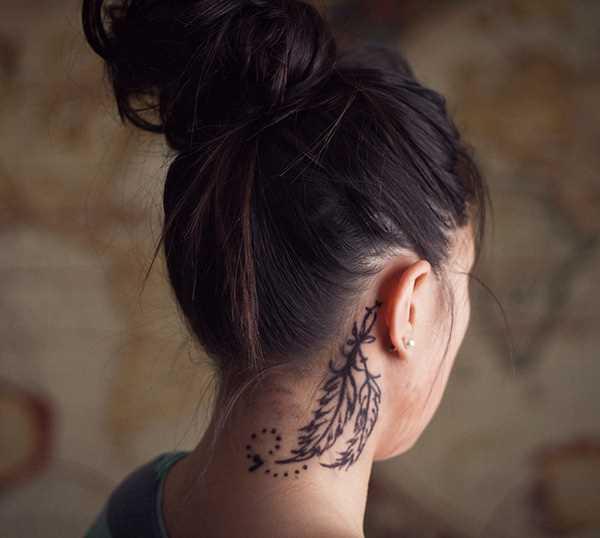 A tatuagem de uma menina em volta do pescoço como um par de penas